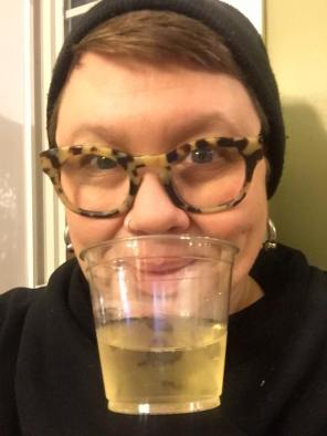 a caucasian butch female person has very short brown hair and a black hat and holds a small plastic cup of champagne with their lips.