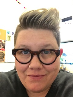 full face shot of a caucasian butch female with a dark roots/silver tips pompadour looks directly into the camera. she has blue eyes, silver earrings, and a black v-neck sweater on.