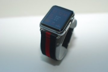Apple Watch with silver accents with a black and red striped band