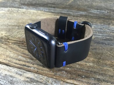 Black apple watch with black leather band featuring blue stitching