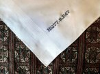 a white hankie on a patterned multi color background reads HQ77.9.B47