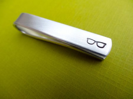a silver tie bar with black etched glasses at the far right end sits on a bright green backdrop