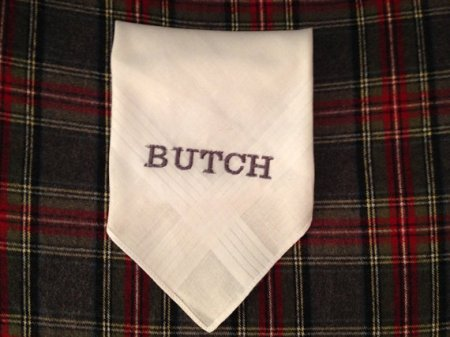 a white folded hankie is sitting on a plaid background with the word BUTCH embroidered in the center
