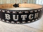 Black belt with silver stitching and accents reading BUTCH sits on a wooden surface